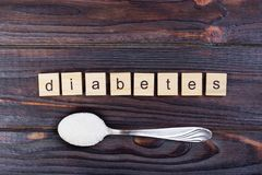 Diabetes block wooden letters and sugar pile on a spoon. Diabetes block letters in crossword and sugar pile on a spoon Royalty Free Stock Images