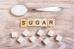 Diabetes block wooden letters with Refined sugar and sugar pile on a spoon.  Royalty Free Stock Image