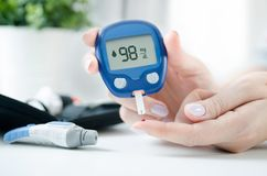 Woman checking blood sugar level by glucometer Royalty Free Stock Photos
