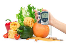 Diabetes concept glucose meter in hand fruits, vegetables Royalty Free Stock Photos