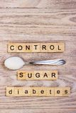 Diabetes control block wooden letters and sugar pile on a spoon Royalty Free Stock Photography