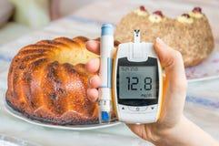Diabetes, dieet en ongezond het eten concept De hand houdt glucometer stock afbeelding