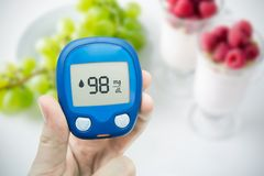 Diabetes doing glucose level test. Fruits in background Royalty Free Stock Photos