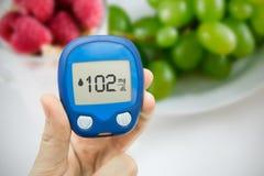 Diabetes doing glucose level test. Fruits in background Royalty Free Stock Image