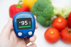 Diabetes doing glucose level test. Vegetables in background Stock Photos