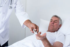 Diabetes masculina de la prueba del doctor del hombre mayor en el metro de la glucosa fotografía de archivo