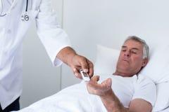 Diabetes masculino dos testes do doutor do homem superior no medidor da glicose fotografia de stock