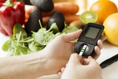 Diabetes monitor, diet and healthy food eating nutritional concept with clean fruits and vegetables with diabetic measuring tool. Kit stock images