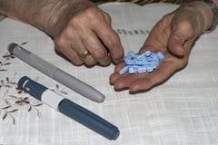 Diabetes oude dame die naalden voorbereiden om haar dosis insuline in te spuiten stock afbeeldingen