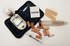 Diabetes paraphernalia. Isolated shot of diabetes paraphernalia including accuchek, needles, sharps contianer and medication stock photos