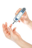 Diabetes patient measuring glucose level blood test. Using mini glucometer and small drop of blood from finger test strips isolated on a white background Stock Photo