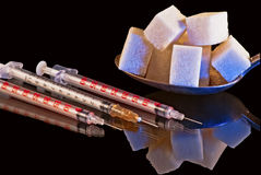 Diabetes: a syringe and sugar Royalty Free Stock Image