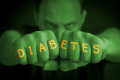 DIABETES written on an angry man's fists. DIABETES written on the fingers of an angry man's fists. Green colored. Message concept image Royalty Free Stock Photo