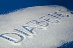 DIABETES written with sugar. Sugar on a blue background with warning message DIABETES written on it. Health concept. Diabetes hazard Royalty Free Stock Image