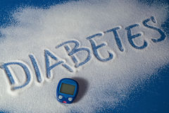 DIABETES written with sugar. Sugar on a blue background with warning message DIABETES written on it. Health concept. Diabetes hazard Stock Photos