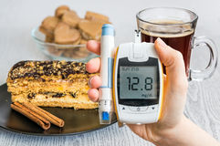 Diabetes y concepto malsano de la consumición La mano sostiene glucometer y los dulces imagen de archivo