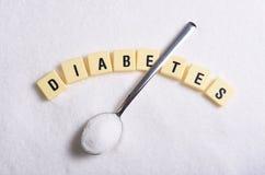 Diabetesblokletters in kruiswoordraadsel en lepel over suikerstapel op korrelige witte suikertextuur wordt geïsoleerd in zoet voe Stock Afbeelding