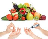 Diabeteskonzept-Glukosemeter in der Hand und gesundes biologisches Lebensmittel Stockbild