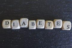 Diabeteswoord op houten kubussen wordt geschreven die stock afbeeldingen