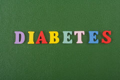 DIABETETES word on green background composed from colorful abc alphabet block wooden letters, copy space for ad text Royalty Free Stock Image