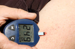 Diabetic. Using a device to measure blood sugar levels stock image