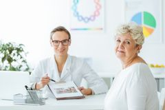 Diabetic during appointment with nutritionist. Diabetic during appointment with professional nutritionist holding a diet plan in the clinic Royalty Free Stock Photo