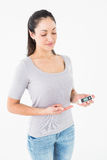 Diabetic brunette holding blood glucose monitor Stock Images