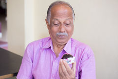 Diabetic craving. Closeup portrait of elderly gentleman in pink shirt craving dessert, eager to eat, isolated indoors background stock photos