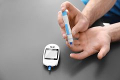 Diabetic man using lancet pen and digital glucometer. On grey background Royalty Free Stock Photos