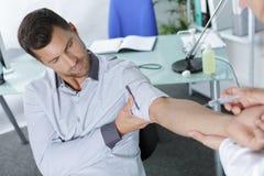 Diabetic man receiving injection in arm. Diabetic men receiving injection in his arm Stock Images