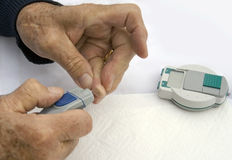 Diabetic senior man checking sugar levels. Closeup of diabetic senior male's hands while he is checking his sugar levels Royalty Free Stock Image