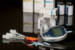 Diabetic Supplies. Including syringes, blood tester and test strips, multi-dose viles of insulin, test strip containers and insulin boxes blurred in background stock photo
