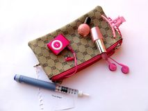 Diabetes syringe pen with bag and accessories. Diabetic syringe with bag and lipstic, nail polish, earrings, mp3 player stock photos