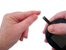 Diabetic Uses Glucometer. To properly check blood glucose levels.  Hands isolated over white Stock Images