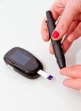 Diabetic woman testing her blood sugar stock images