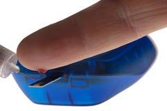 Diabetiker prüft Blutzuckerspiegel mit Messinstrument stockfotografie