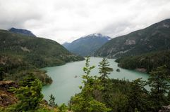 Diablo Lake, Washington Surrounded by Greenery. Diablo Lake with snow-capped mountains in background and  green lush hills in foreground Stock Image