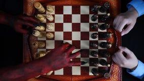 Diablo y hombre de negocios que juegan a ajedrez