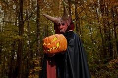 Diabo na floresta escura com abóbora fotos de stock royalty free