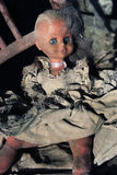 Diabolical doll sitting on an old chair Stock Images