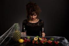 Diabolical młodej dziewczyny obsiadanie przy stołem z owoc zakrywać z pająk siecią Zdjęcia Stock