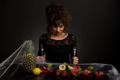 The diabolical young girl sitting at a table with fruits covered with spider web. Female stylized Addams Family waiting for a meal with fruit and vegetables Stock Photos