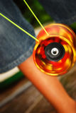 Diabolo. A red Diabolo is spinning quickly on a yellow string Stock Photo