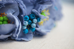 Diadem of blue flowers on white wooden surface Stock Photos