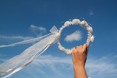 Diadem of flowers on hand and blue sky background Royalty Free Stock Photography