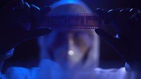 Diafilme de observação do assistente de laboratório, procurando a evidência contra o criminoso filme