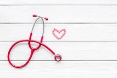 Diagnóstico y curación de la enfermedad cardíaca con el estetoscopio y del símbolo femenino en la maqueta de madera blanca de la  foto de archivo