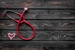 Diagnóstico y curación de la enfermedad cardíaca con el estetoscopio y del símbolo femenino en maqueta de madera de la opinión su fotografía de archivo