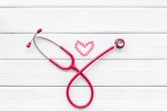 Diagn?stico y curaci?n de la enfermedad cardiaca con el estetoscopio y del coraz?n en la maqueta de madera blanca de la opini?n d foto de archivo