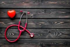 Diagn?stico y curaci?n de la enfermedad cardiaca con el estetoscopio y del coraz?n en maqueta de madera de la opini?n superior de fotos de archivo libres de regalías